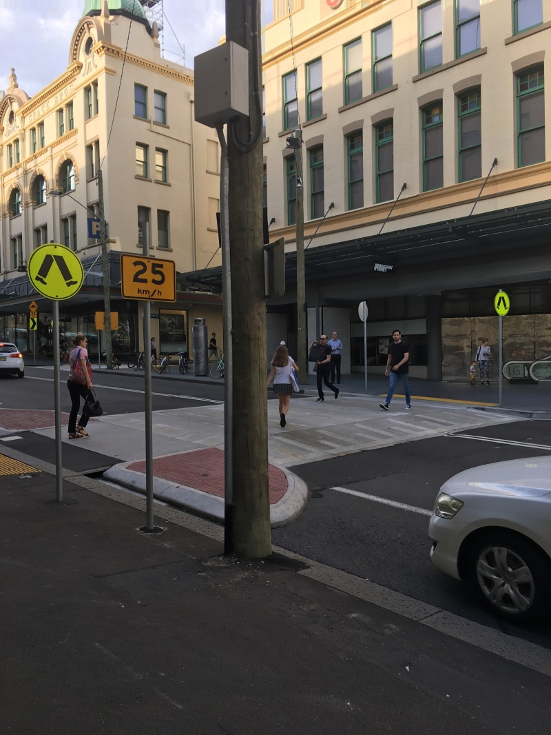 A midblock raised crosswalk/speed hump at the busy entrance to the Broadway Shopping Center. This is excellent, and cars reluctantly yield to the dominant pedestrian. The walk leads to escalators. (Mid-right)