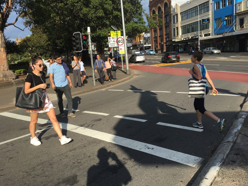 A signalized but porkchop-islanded crosswalk at a Free Left (Free Right for those in the right-side drive countries). Notice the pedestrian light is red (don't walk) but the pedestrians cross anyway. If the free left is not eliminated in a more comprehensive redesign, it could easily be de-signaled and the crosswalk raised, so pedestrians dominate, and cars travel when they can.
